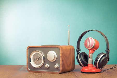 Retro radio, rode microfoon, koptelefoon op tafel oude stijl foto
