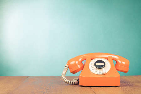 contact center: Retro orange telephone on table front mint green wall background Stock Photo