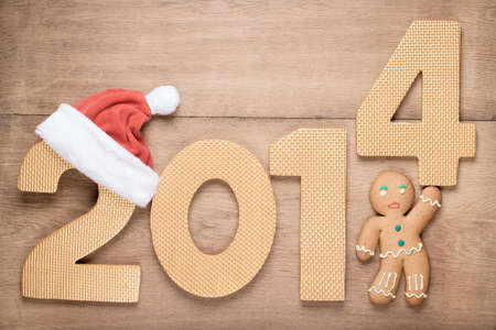 Concept greeting card with 2014 date and Gingerbread Man on old wood background