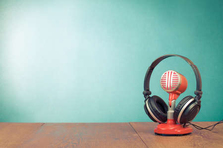 Retro red microphone and headphones on table front mint green background