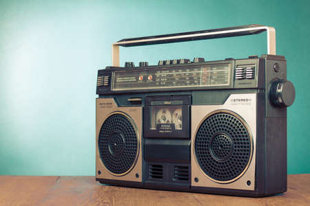 Retro ghetto blaster cassette tape recorder on table in front mint green background 版權商用圖片