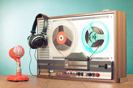 Retro reel to reel tape recorder, microphone, headphones in front mint green background