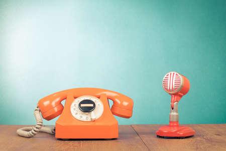Retro microfono rosso e telefono sul tavolo davanti a sfondo verde menta