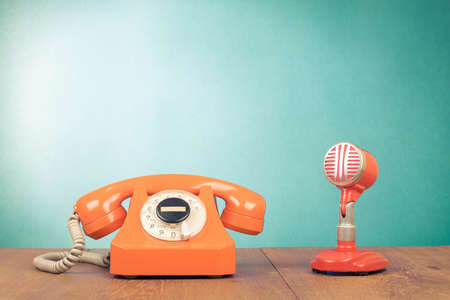 Retro red microphone and telephone on table front mint green background Standard-Bild
