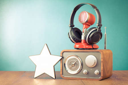 Retro radio, red microphone, headphones and win star in front aquamarine wall background
