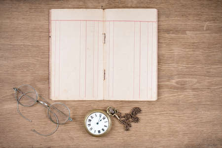 Old note book, eye glasses and pocket watches on wooden table background