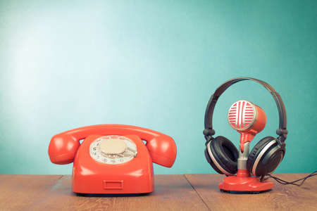 Retro red microphone, headphones and telephone on table front mint green background