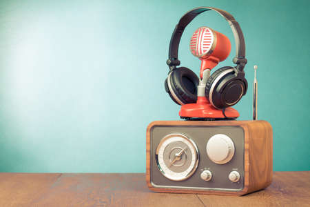 commentator: Retro radio, red microphone, headphones on table old style photo
