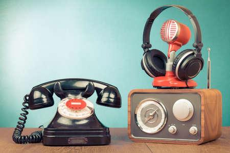 Retro roterende telefoon, radio, hoofdtelefoon, microfoon op tafel