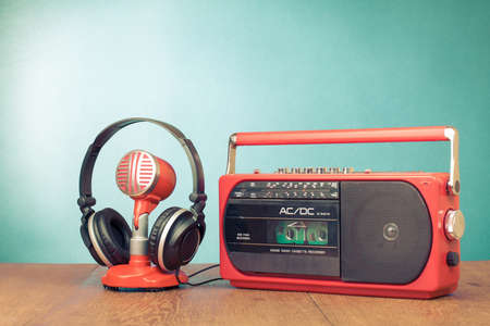 Retro red radio cassette player, microphone, headphones on table