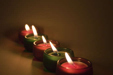 Five red and green lit little candles in a row. Christmas colors
