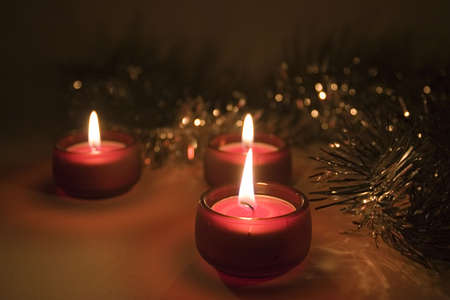 Three lit little red candles and christmas ornament