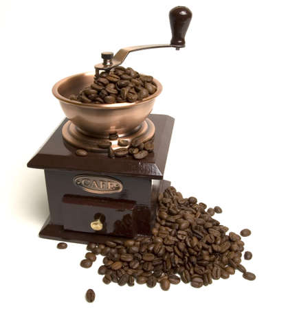 Vintage coffee grinder with coffee beans around it Stock Photo