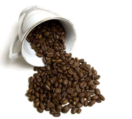 Laying coffee cup with spilled coffee beans Stock Photo