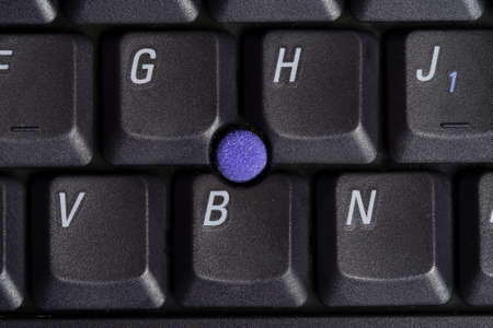 Macro shot of laptop keyboard with point stick surrounded by some keys.