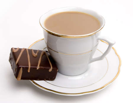 Sweet chocolate square pastry on a white saucer next to coffee cup.