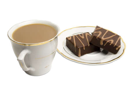 Coffee in a cup next to delisious chocolate square pastries on a saucer. Cup and saucer both have matching golden edges. . Stock Photo