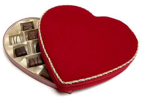 Red heart shaped velvet candy box with candies (half open) with . Valentines day gift