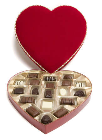 Red heart-shaped open candy box with candies for Valentines Day. .