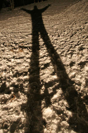 Long and spooky looking shadow of a man on the snow