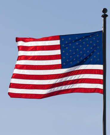 Waving american flag over a blue sky