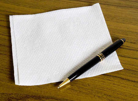 Blank napkin for your message on wooden table and a pen
