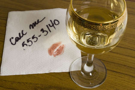 Glass of white wine and a napkin with phone number and lipstick Stock Photo