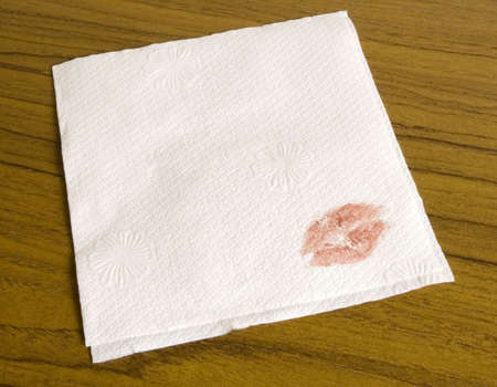 Blank cocktail napkin for your message. With a lipstick imprint in the corner