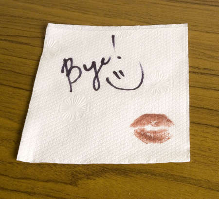 Word Bye, lipstick and a smiley face on the napkin Stockfoto