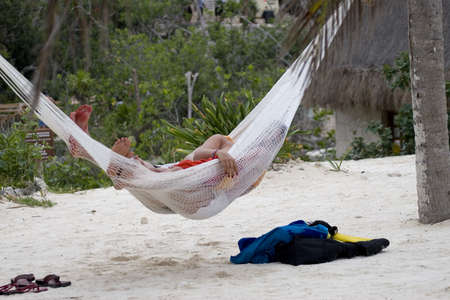A couple lazily laying in the hammock at the beach photo