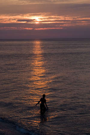 Silhouette of a woman bathing in the calm waters looking at the setting sun