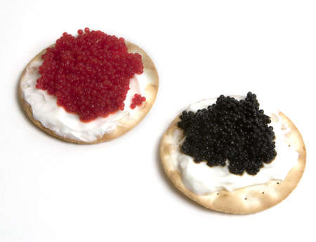 Fancy black and red caviar with sour cream on top of crackers Stock Photo