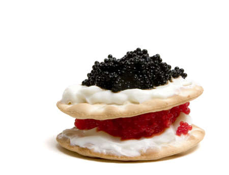 Red and black caviar with sour cream on crackers, layered on top of each other, making it look like a cake. Isolated on white includes clipping path.  photo