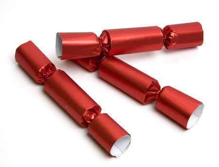 Three red Christmas English party crackers isolated over white. Party Crackers are an old English party favor idea and tradition. They are festively wrapped cardboard cylinders that can be filled with all manner of treasures and trinkets and tied off at t