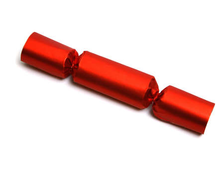 pyro: Closeup of a single red Christmas English party crackers isolated over white. Lost of space for your text or design. Party Crackers are an old English party favor idea and tradition. They are festively wrapped cardboard cylinders that can be filled with all manner of treasures and trinkets and tied off at the ends. A cracker snap is inserted which, when pulled from both ends, pops loudly. Stock Photo