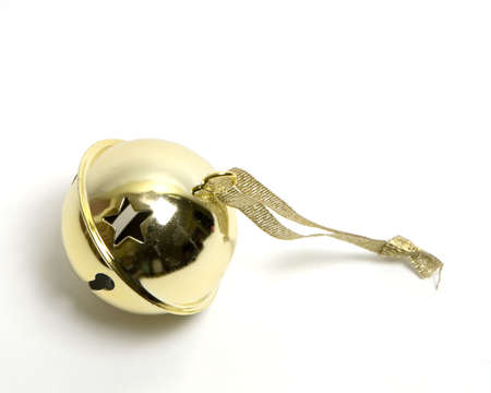 Single golden little metal bell with stars punched in it for decorating a christmas tree, with sparkling ribbon attached to it. Isolated over white