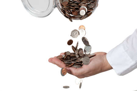 a lot of money: Pouring a lot of change (coins) from the jar into a hand. Isolated against white background.