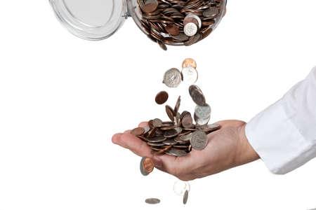 mucho dinero: Vertiendo una gran cantidad de cambio (monedas) de la jarra en la mano. Aislada contra el fondo blanco.