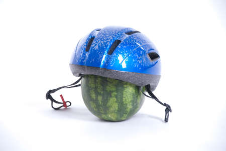 Watermelon with a bicycle helmet shows safety when cycling Stock Photo