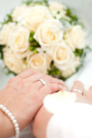 Hands with wedding rings from a newly married couple and bouquet