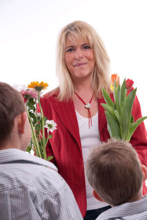siblings give their mother a gift for Mothers Day Stock Photo