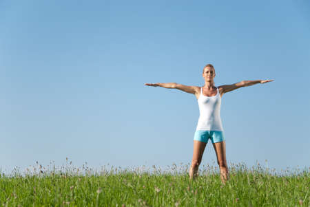 Young woman is doing fitness exercise in the nature Stock Photo