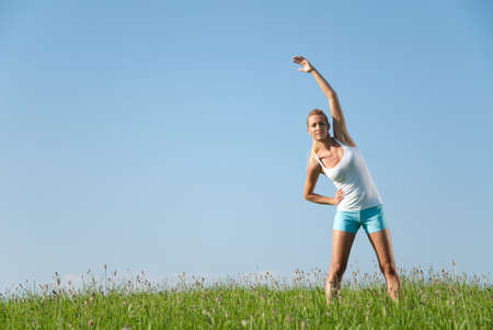 exertion: Young woman is doing fitness exercise in the nature Stock Photo