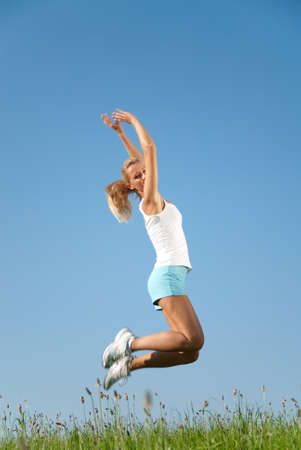 young woman jumping in the air against a blue sky