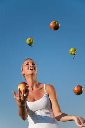 young woman juggling with healthy food outdoors