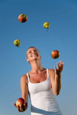 exertion: young woman juggling with healthy food outdoors