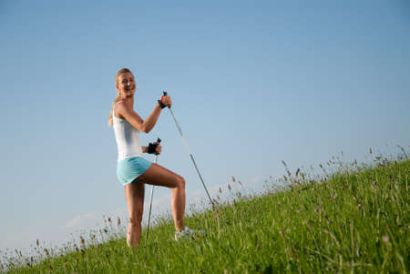young goes woman nordic walking in her spare time in the nature photo