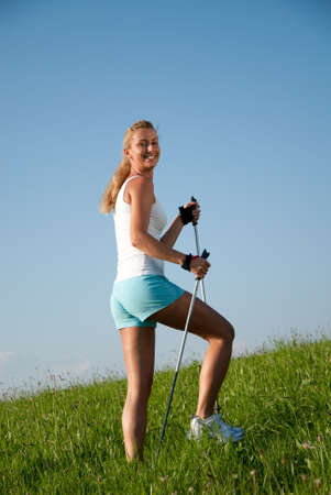 spare time: young goes woman nordic walking in her spare time in the nature