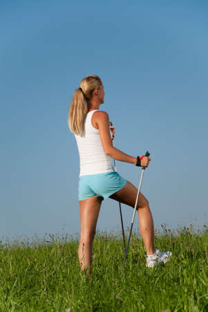 young goes woman nordic walking in her spare time in the nature