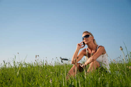 summer clothing: young woman communicates by phone outdoors Stock Photo